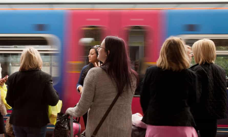A group of women on the platform catching a train.