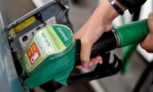 A person filling up their car with unleaded petrol