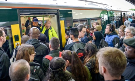 Passengers wait to board a crowded Southern train – some have reported losing their jobs due to repeated delays.