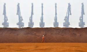 A worker walks past a pile of iron ore at a port in Tianjin, China