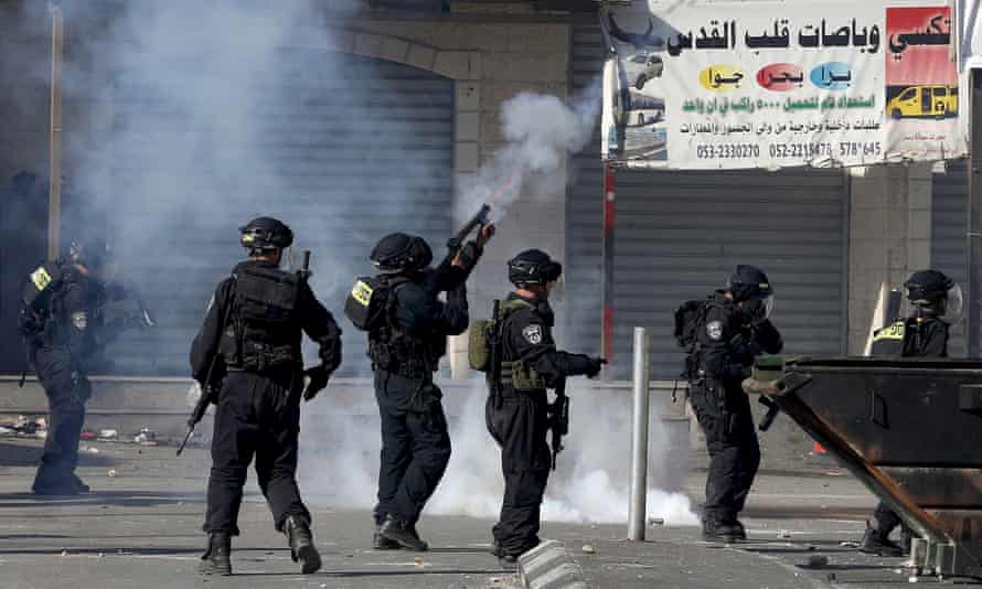An Israeli officer fires teargas during clashes with Palestinian stone-throwers near Jerusalem.