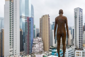 An Antony Gormley 'naked man' scultpure perched on the ledge of a skyscraper in Hong Kong