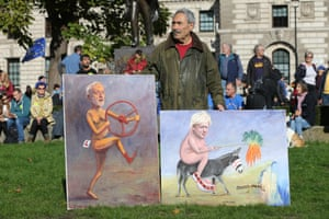 Satirical artist Kaya Mar holds two of his latest political works outside the Houses of Parliament.