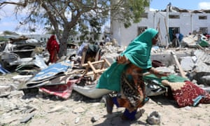 A woman runs past the debris at the site of a blast in the district council office of Hawlwadag in Mogadishu, Somalia