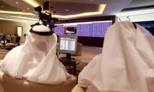 Traders monitoring screens displaying stock information at Qatar Stock Exchange in Doha today.