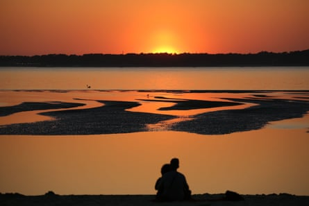 People watch the sunset on the Cap Ferret, from a beach of the Arcachon Bay