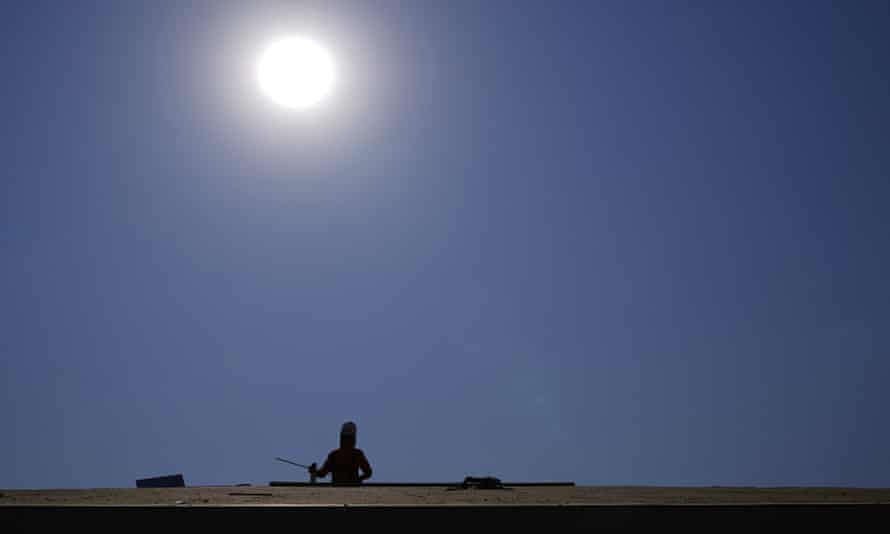 A roofer works under the baking sun on 17 June in Phoenix.