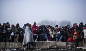 People wait to enter Austria at the country's border with Slovenia