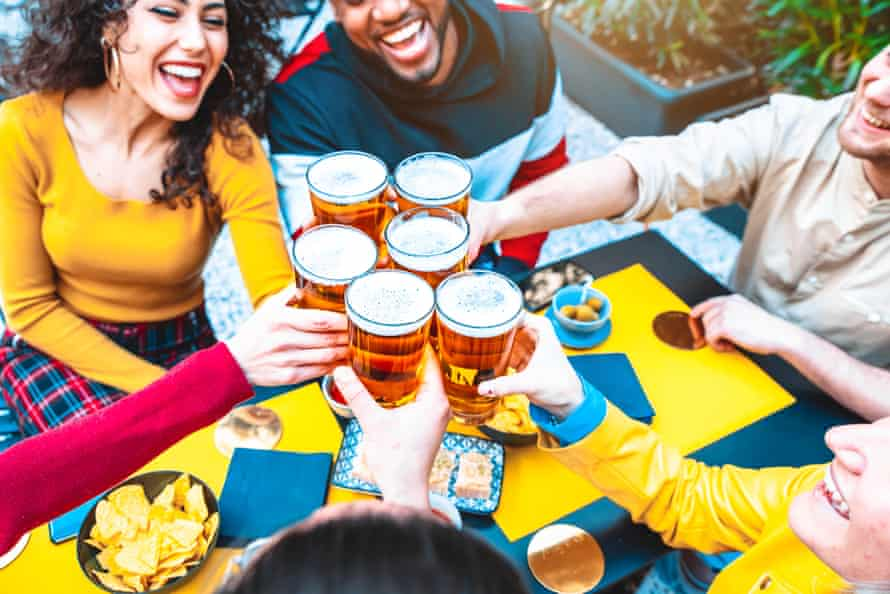 Group of multicultural friends drinking and toasting beer at brewery bar restaurant - Happy people having fun at rooftop home party - Vivid color filter, focus on glasses