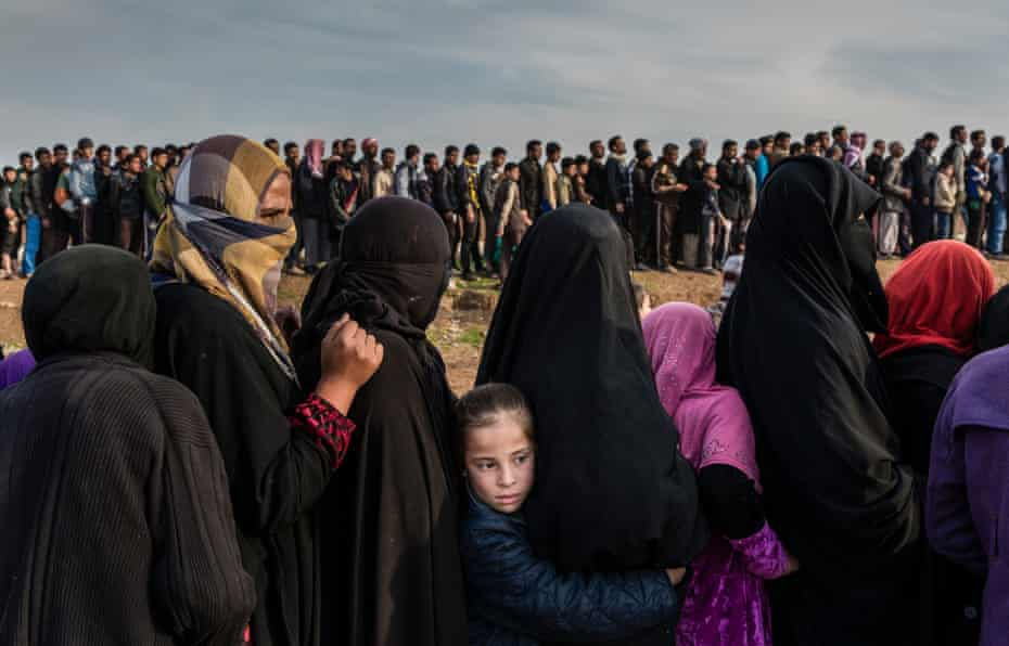 Civilians who had remained in west Mosul during the battle to retake the city lining up for an aid distribution in the Mamun neighbourhood, Iraq, March 2017.