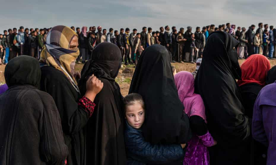 Civilians who had remained in west Mosul during the battle to retake the city, lining up to receive aid, Iraq 2017.
