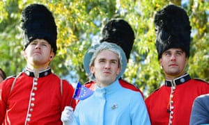 A not very convincing Queen Elizabeth II lookalike flanked by some Coldstream guards.