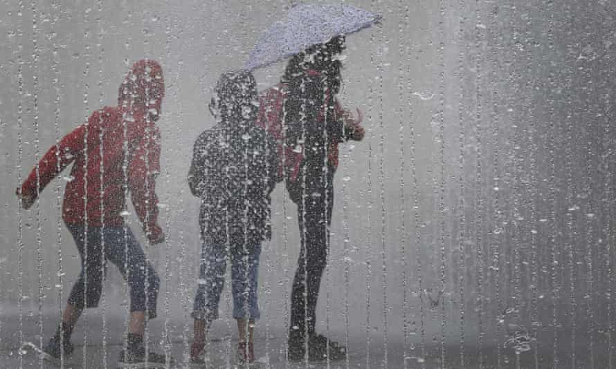 Children play in the rain with an umbrella