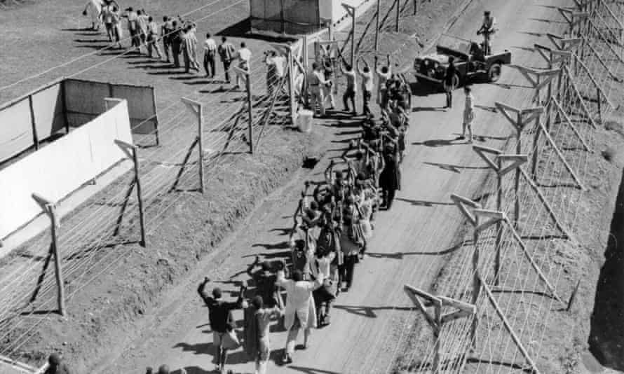 Suspected Mau Mau militants opposed to the British rule of Kenya are marched into a detention camp in 1954.