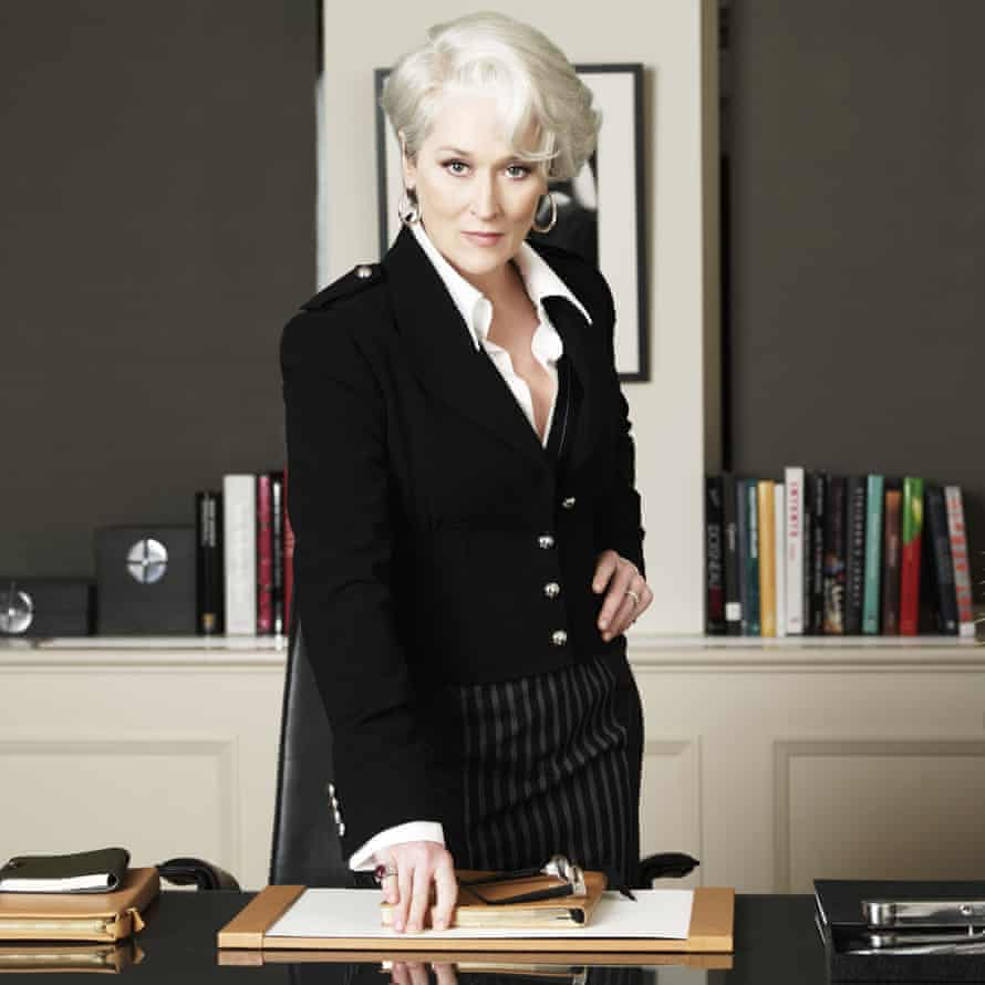 Meryl Streep, one hand on her hip and the other on a desk, looking severe and efficient in The Devil Wears Prada
