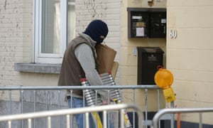 A Belgian police officer enters the apartment building in the Forest area of Brussels where a routine search led to a shootout on Wednesday.