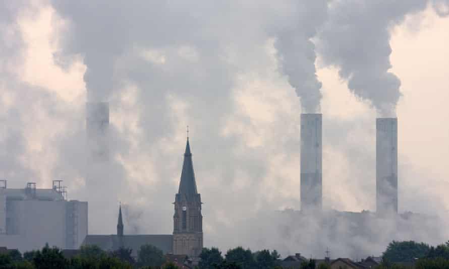 A Catholic church spire against smoky coal power plants in North Rhine-Westphalia, Germany