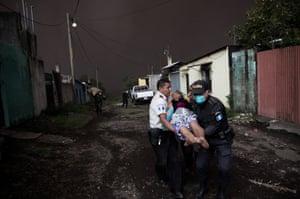 Police help a woman to evacuate in the village El Porvenir