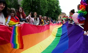People hold a huge rainbow flag during the York Pride parade on 9 June in York, England.