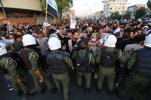 Iraqi police officers stand guard as demonstrators holding banners gather to protest in central Baghdad.