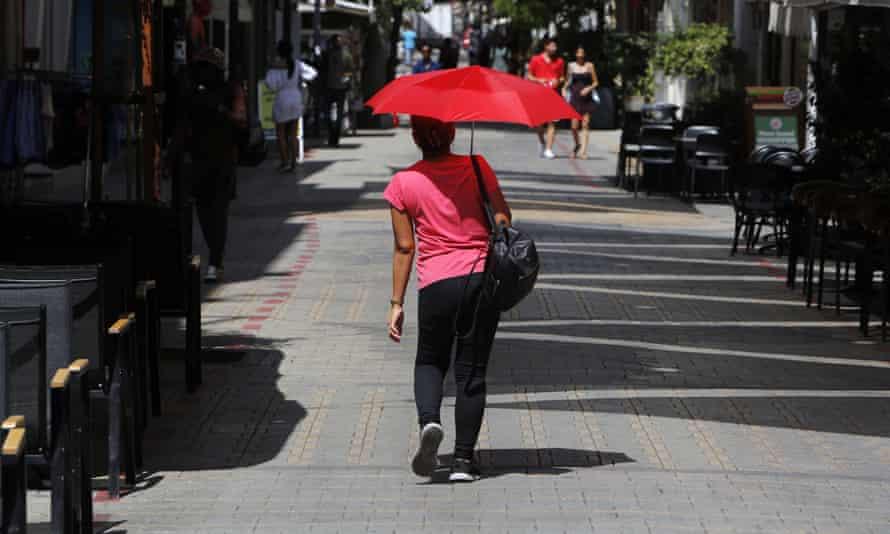 Woman holding umbrella in Cyprus sun