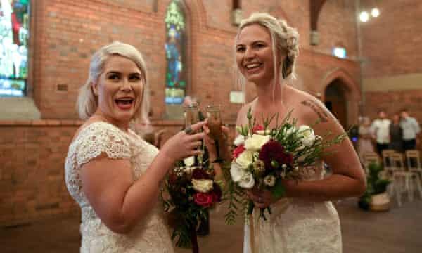 Twee vrouwen in trouwjurken, lachend en champagneglazen klinkend