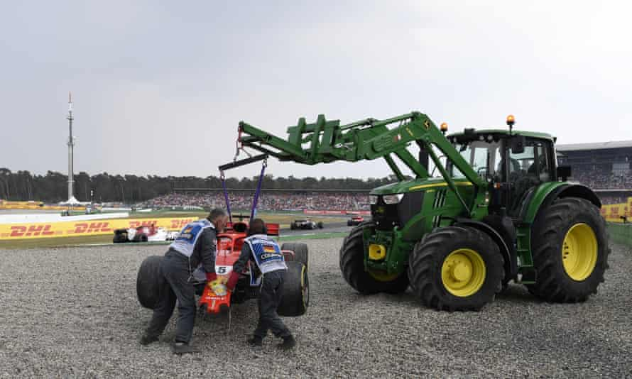 Track marshals collect debris and the car of Ferrari driver Sebastian Vettel after he crashed at the Hockenheimring.