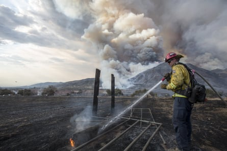 A firefighter works on hotspot at a wildfire in Yucaipa, California.
