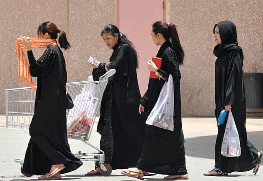 Filipina maids wearing black cloaks carrying shopping bags in Riyadh.