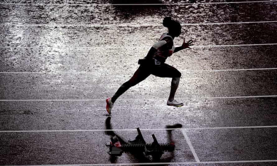 Kadeena Cox runs in the rain at Tokyo National Stadium.