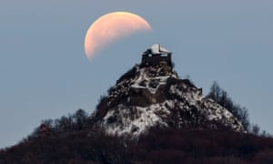 The moon, fully shadowed by the Earth, is seen above the castle of Salgo near Salgotarjan, Hungary
