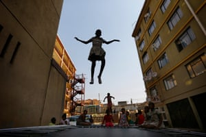 A schoolgirl hangs in mid-air as she jumps on one of the three trampolines at the Alexandra trampoline club after school in the impoverished township.