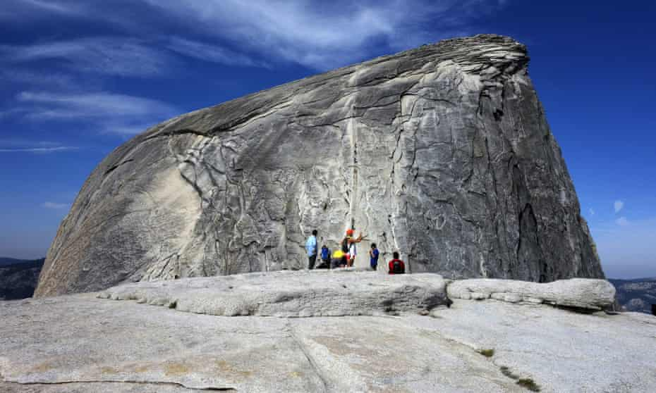 Hikers gather as climbers use the assistance of cables to scale Half Dome in Yosemite national park.