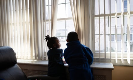 Marley Major, 4, and her brother Max, 5, look out a window of their home in Mount Vernon, New York.