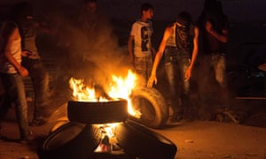 Teenagers from al-Am'ari refugee camp in Ramallah burn tyres during clashes with Israeli troops at the Qalandia checkpoint