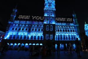 People watch a sound and light show at the Grand Place in Brussels, Belgium