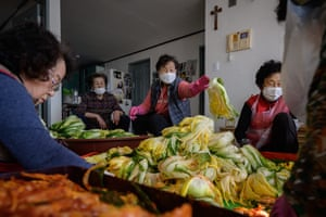 The friends prepare the cabbages to make kimchi while Lee Young-ja (second left) looks on
