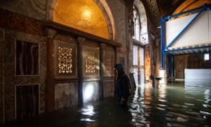 A police officer checks damage inside St Mark's Basilica on 15 November