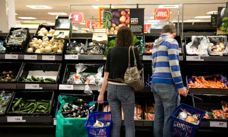 Shoppers browse a veg aisle at Sainsbury's