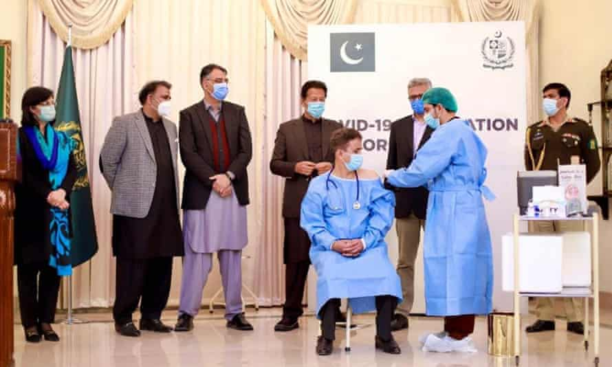 Pakistan's prime minister Imran Khan, back row, third from right, watches as Chinese vaccine is administered to health workers last month.