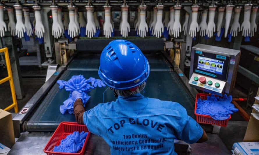 A worker inspects disposable gloves at the Top Glove factory in Shah Alam on the outskirts of Kuala Lumpur. The US will seize products made by Malaysia's Top Glove, officials said on 29 March.