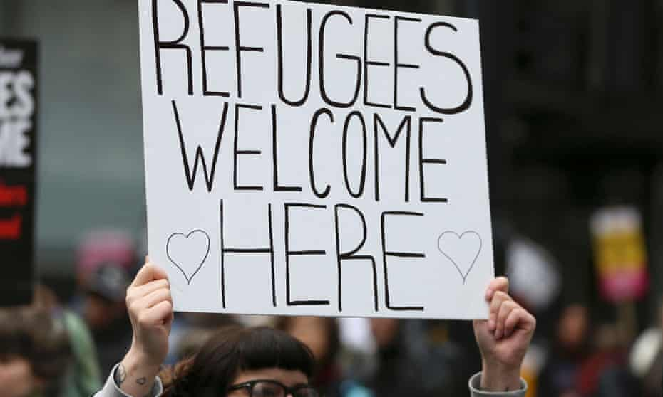 A protester holding a 'Refugees Welcome' sign