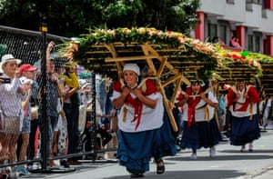 Medellín, Colombia Silleteros haul enormous flower arrangements during the traditional flower festival parade