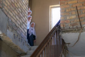 Schoolgirls peer from behind a wall after arriving at a gender-segregated school in Kabul, Afghanistan