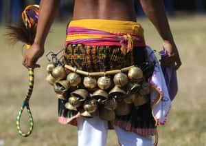 A Manggarai man wearing bells performs during a Caci – a ritual whipping fight – in Bali