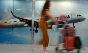 a passenger passes a Thomas Cook poster