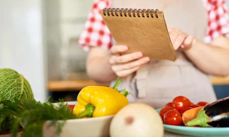 Holding a note pad over some vegetables