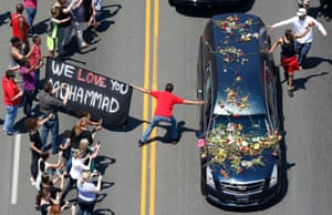 A well-wisher holding a banner touches the hearse carrying the remains of Muhammad Ali