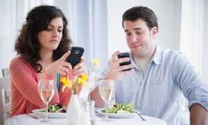 Two diners looking at their phones