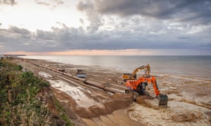 A digger on the Norfolk coast moving sand.